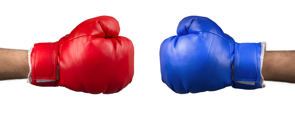 Red boxing glove and blue boxing glove on opposite sides of each other