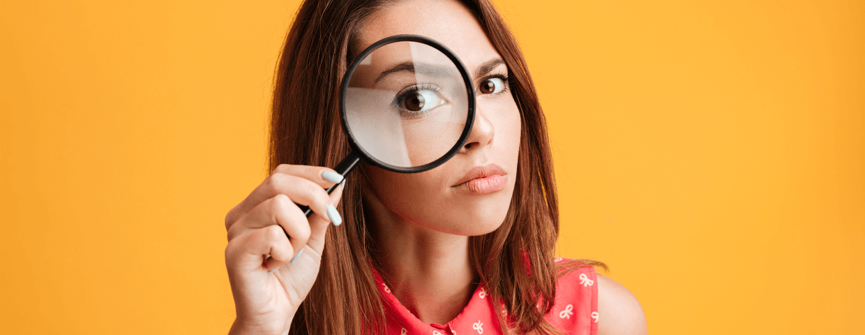 Close-up portrait of young serious woman looking through a magnifying glass, isolated over yellow background