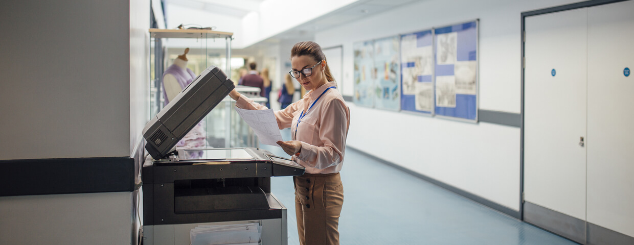 Female teacher standing next to printer in school hallway lifting up the top part of the machine looking at a paper.