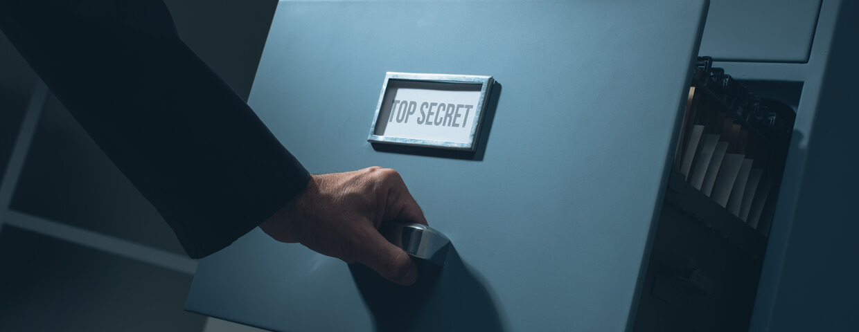 Man pulling out drawer on filing cabinet that says top secret