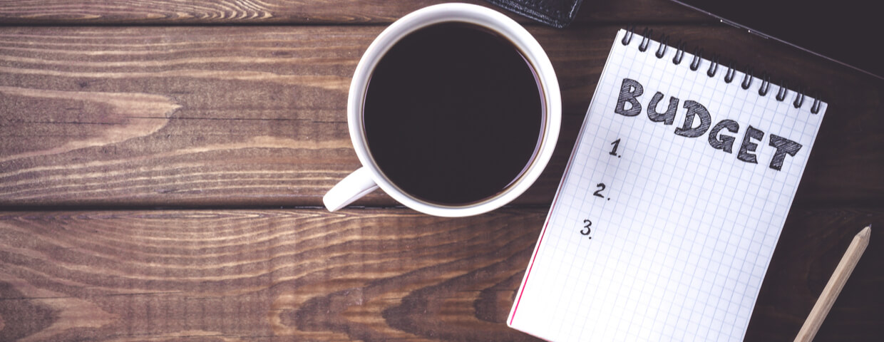 Cup of coffee and note pad with the word budget written on it on table