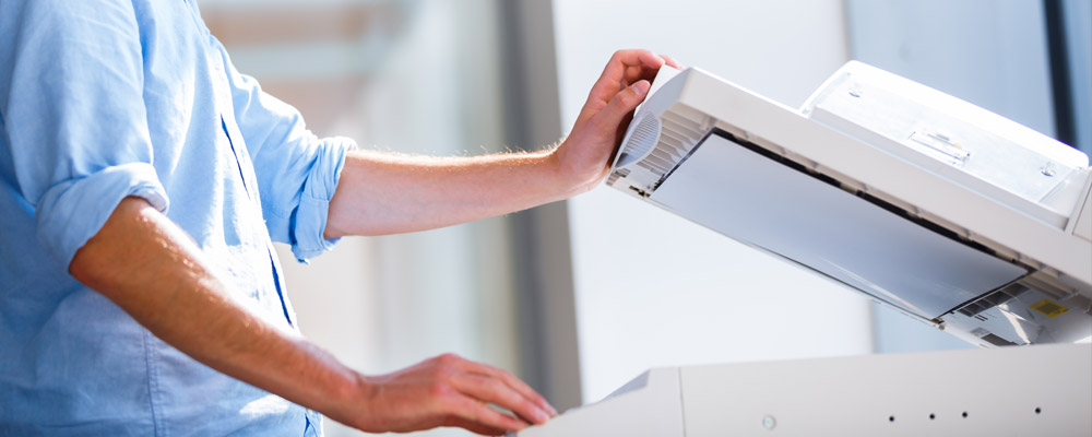 Person standing at the copier with platen cover opened