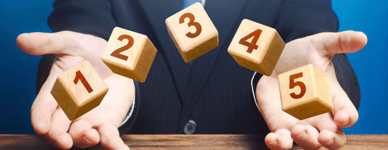 Man holding five blocks with number on each block.