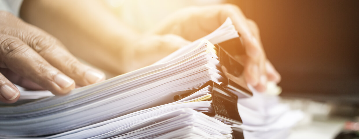 person holding stack of papers