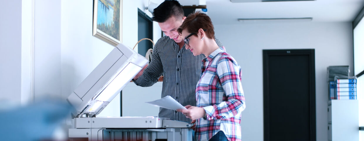 Man and woman in office working at printer